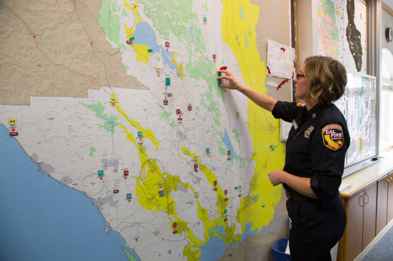 Cal Fire Captain Leah Simmons-Davis moves magnets on a map representing fire fighters. On the night of October 8 Cal Fire staff ran out of magnets for fires and fire crews and had to start using post-its.