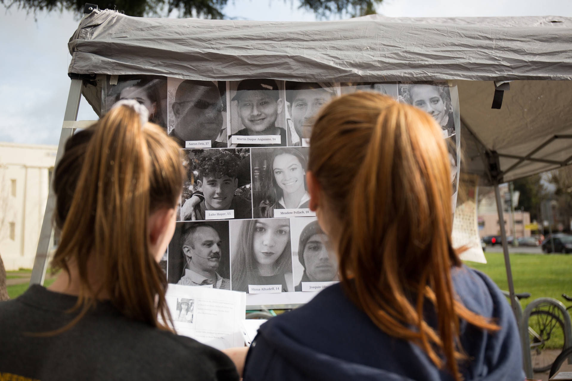 Students at Oakland Technical High School look at a billboard with photos of the 17 victims of the Parkland, Florida, mass shooting during a walkout to protest gun violence on March 14, 2018. Samantha Shanahan/KQED