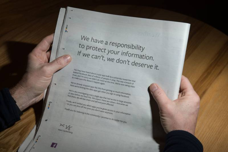 A man reads a full-page advertisment, taken out by Mark Zuckerberg, the chairman and chief executive officer of Facebook to apologize for the large-scale leak of personal data from the social network, on the backpage of a newspaper, in Ripon, England on March 25, 2018. Ads also appeared in the New York Times and Washington Post.