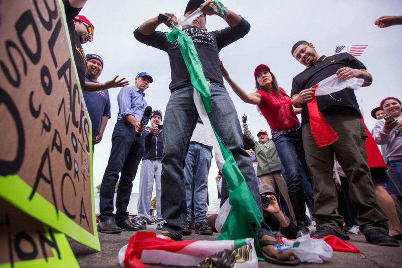 A pro-Trump demonstrator tears up a Mexican flag that was taken from a counter protester as supporters of President Donald Trump rallied during Trump's visit to see border wall prototypes on March 13, 2018 in San Diego.