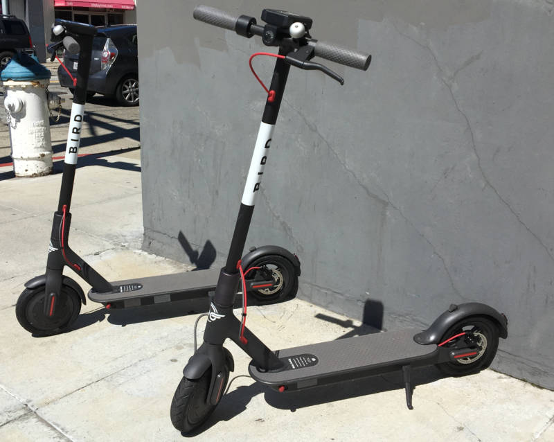 Two scooters from Southern California startup Bird on a sidewalk near Fifth and Brannan streets in San Francisco.