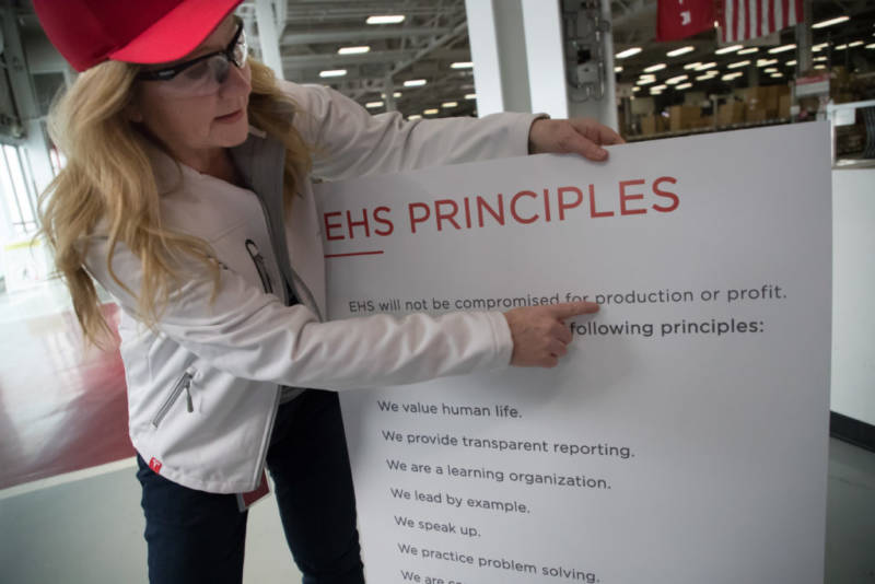 Laurie Shelby, Tesla's vice president for environment, health and safety, points to the principles of her department listed on a placard at the car plant in Fremont.