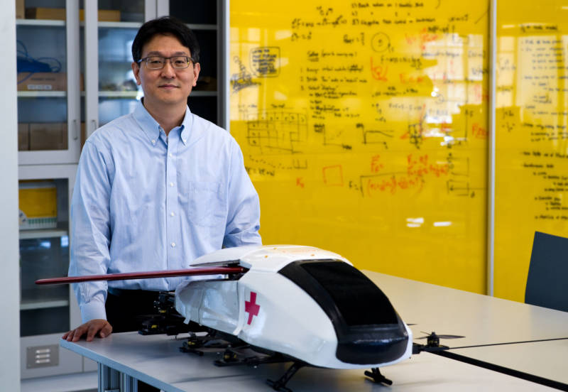 Soon-Jo Chung, associate professor of aerospace at Caltech and a Jet Propulsion Laboratory research scientist, stands behind a scale model of the air ambulance. Its design is modeled on a puffer fish.