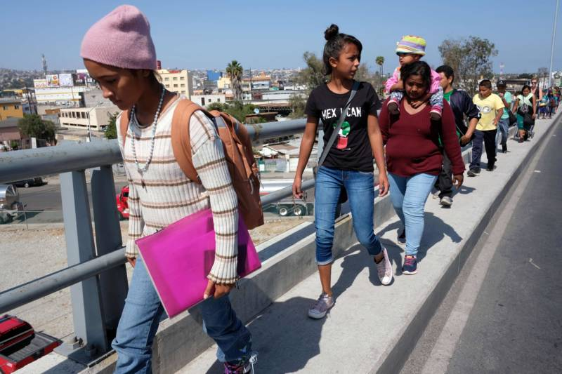 """Central American migrants travelling in the """"Migrant Via Crucis"""" caravan walk to their legal counselling meeting in Tijuana, Baja California state, Mexico, on April 28, 2018. The US has threatened to arrest around 100 Central American migrants if they try to sneak in from the US-Mexico border where they have gathered, prompting President Donald Trump to order troop reinforcements on the frontier."""