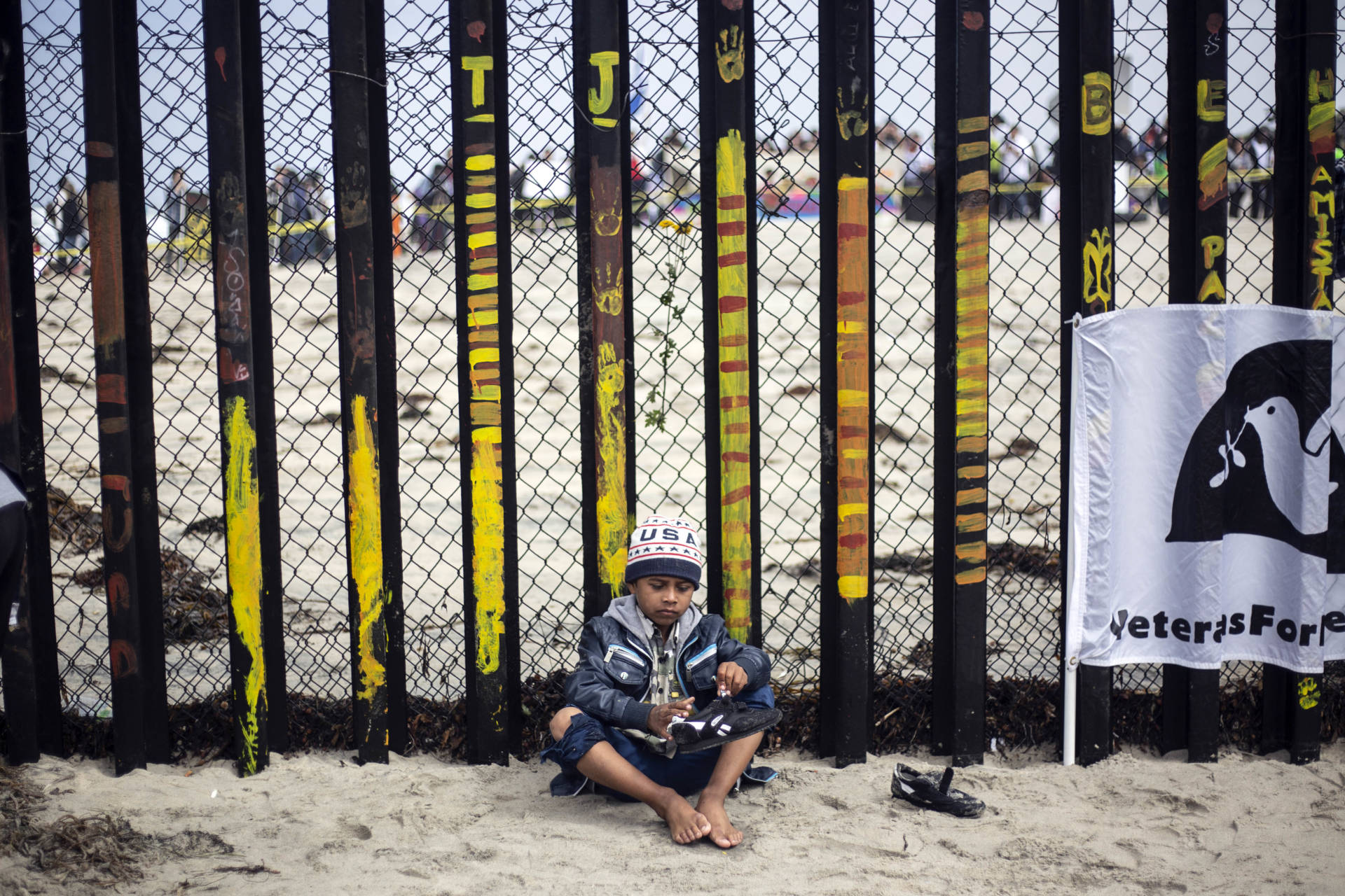 """A Central American migrant boy travelling in the """"Migrant Via Crucis"""" caravan removes sand of his shoes during a demonstration at the US/Mexico Border at Tijuana's beaches, Baja California state, Mexico, on April 29, 2018."""