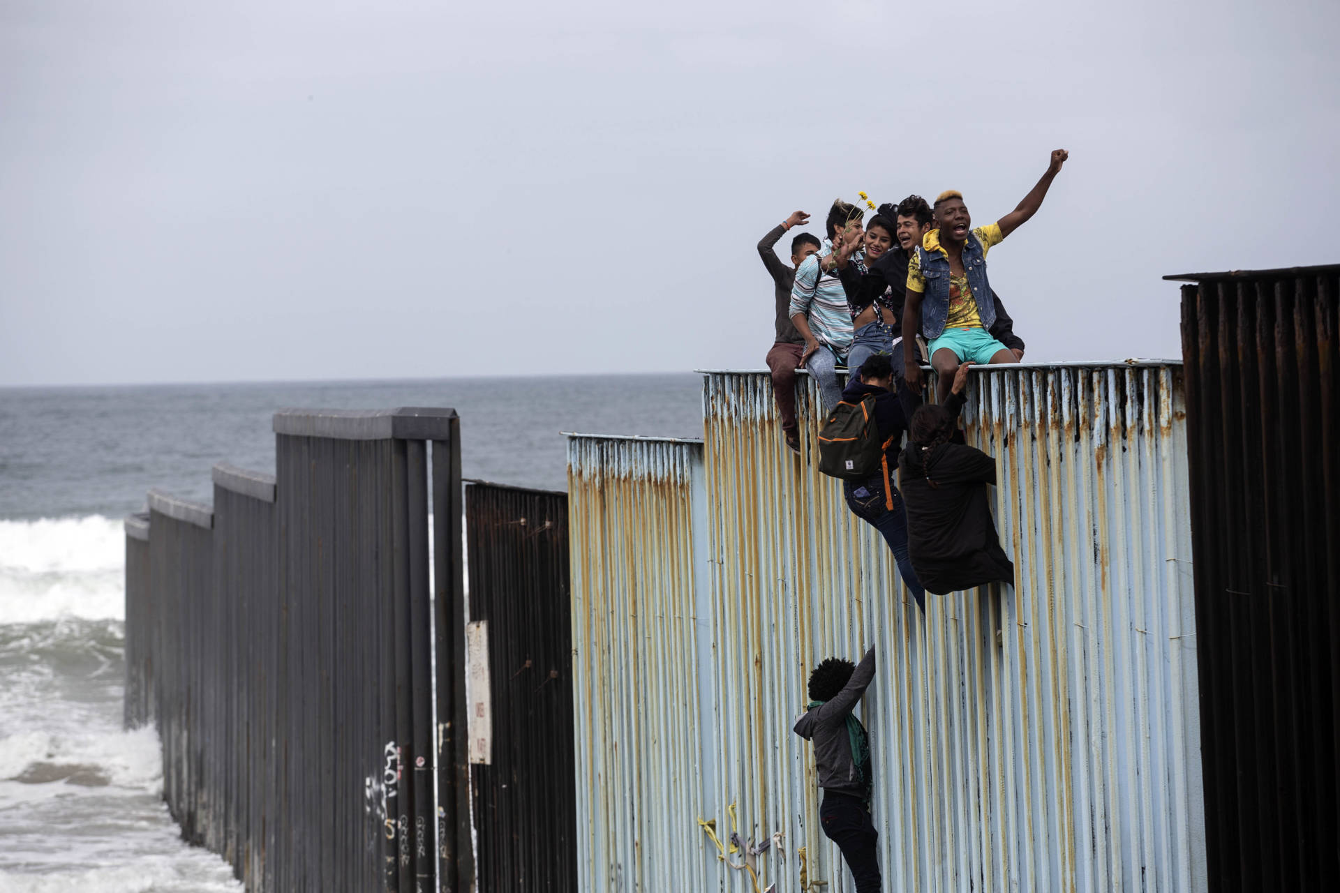 """Some Central American migrants traveling in the """"Migrant Via Crucis"""" caravan climbed the wall to sit and wave signs under the watchful eyes of U.S. Border Patrol agents at the US/Mexico Border at Tijuana's beaches, Baja California state, Mexico, on April 29, 2018."""