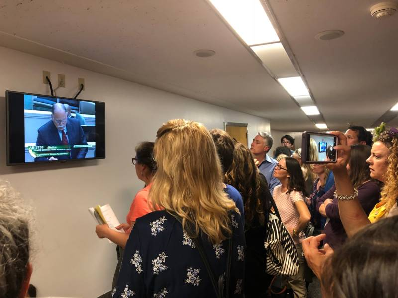 Opponents of AB 2756 crowd around a TV in the hallway to watch Assemblymember Medina introduce the bill.