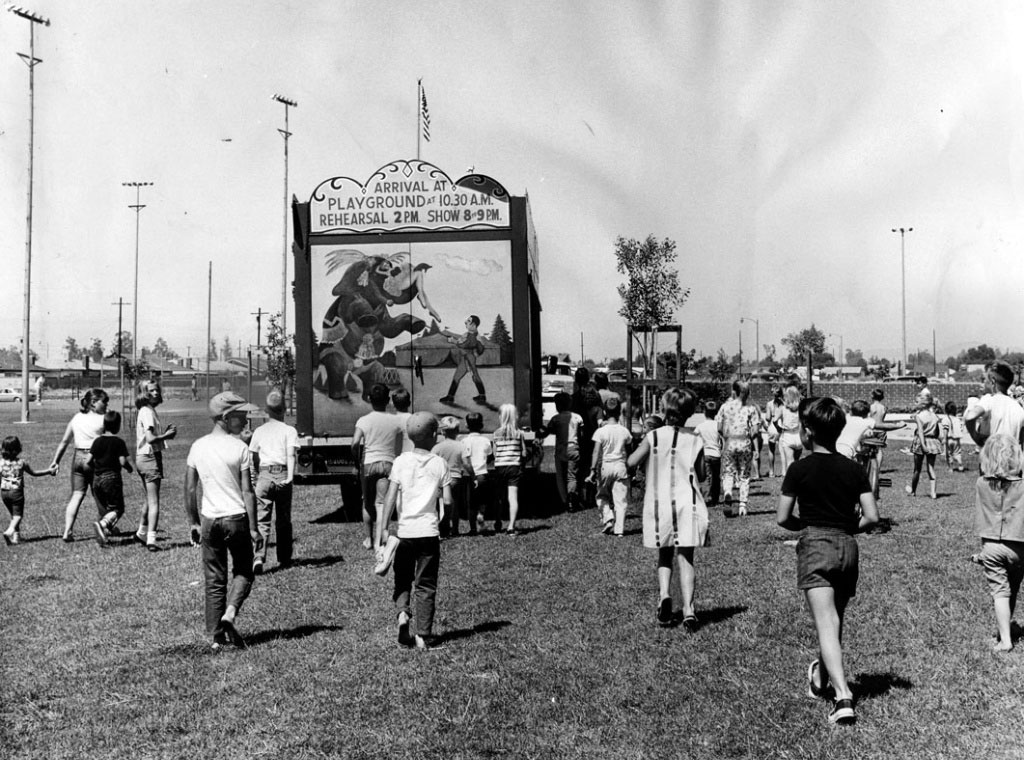 Children follow a truck as it drives into position at Granada Hills Playground to set up the 1964 Combined Traveling Circus and Kiddie Carnival. Photo dated: July 4, 1964.