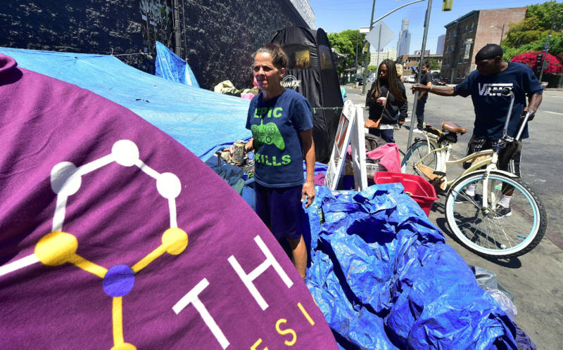 A homeless woman stands in front of her tent near Skid Row in downtown Los Angeles on June 20, 2017.