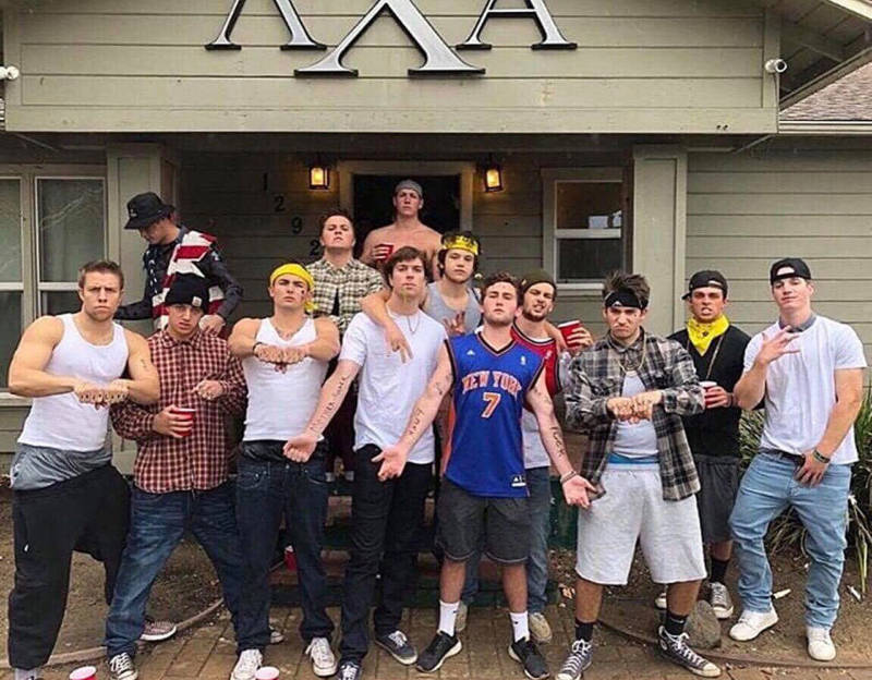 Members of the Cal Poly Lambda Chi Alpha chapter stand in front of their fraternity house dressed as gang members.