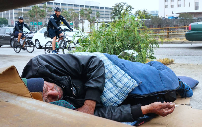 LAPD officers patrol on bicycles past a homeless man in downtown Los Angeles.