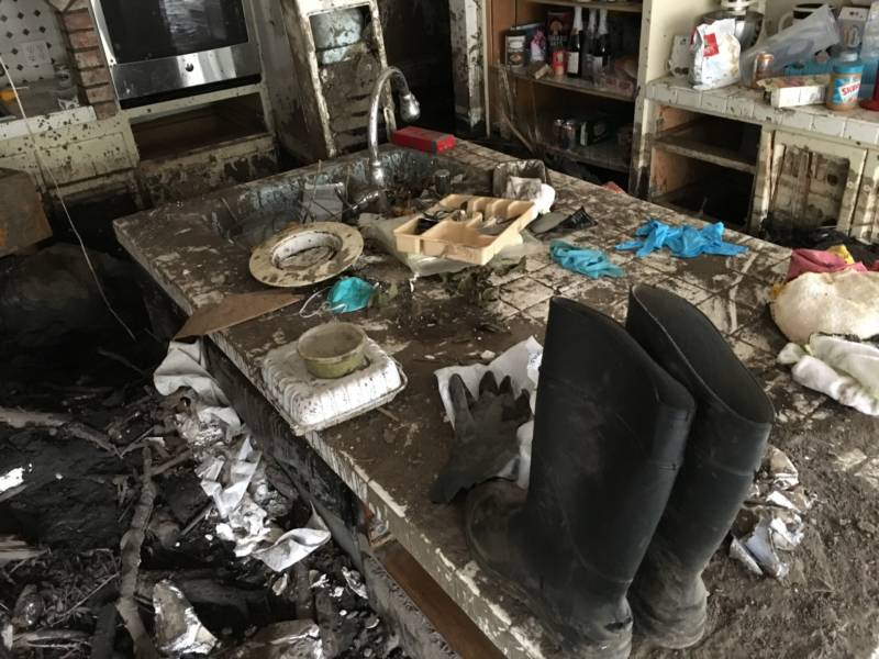Rubber boots and other mud-caked items sit atop a table in Peri Thompson's kitchen. Hers was one of more than 300 homes damaged by a large mudslide in January that followed the devastating December wildfires in Santa Barbara County.