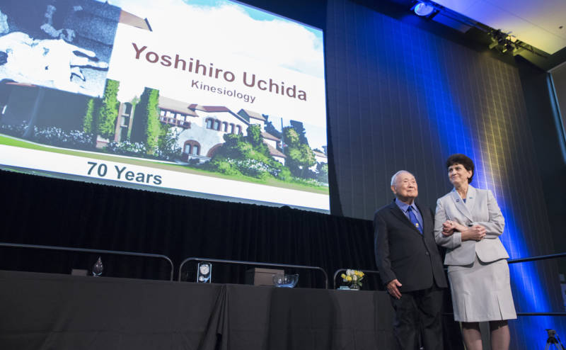 """Coach Yoshihiro """"Yosh"""" Uchida gets a standing ovation at the 2018 San Jose State Faculty Service Recognition and Awards Luncheon, with SJSU President Mary Papazian standing by his side."""