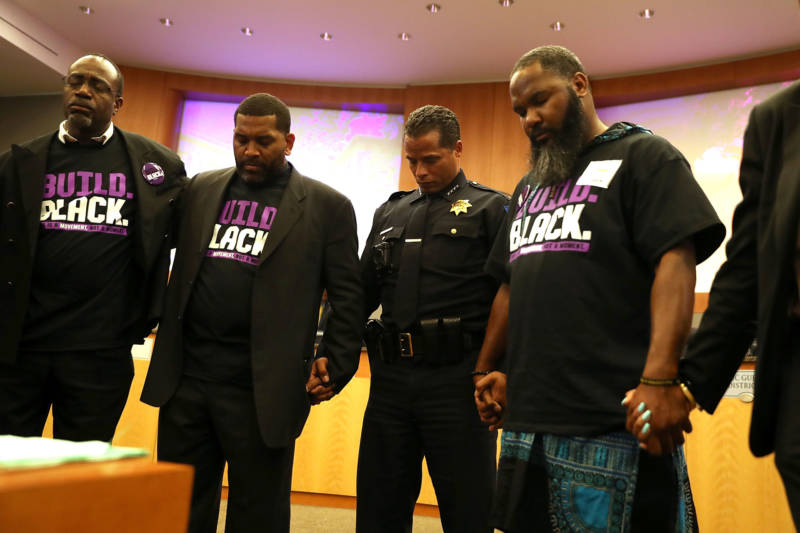 Sacramento police chief Daniel Hahn prays after Stevante Clark, brother of Stephon Clark, disrupted a special city council meeting at Sacramento City Hall on March 27, 2018.