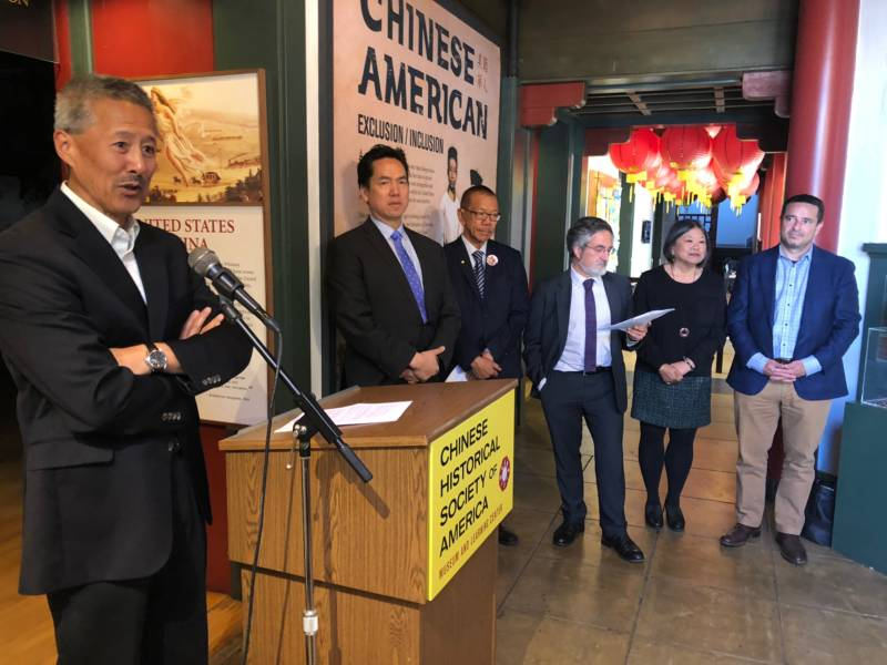 Chinese American Historical Society President Hoyt Zia speaks at a press conference as supervisors and other officials look on.