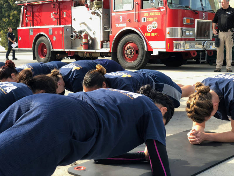 Candidates at the Women's Fire Prep Academy attempt to hold plank position for four minutes.