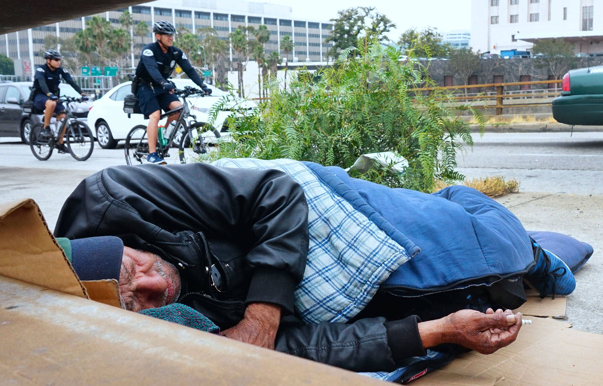 A homeless man sleeps at his encampment on a downtown sidewalk in Los Angeles. Frederic J. Brown/Getty Images