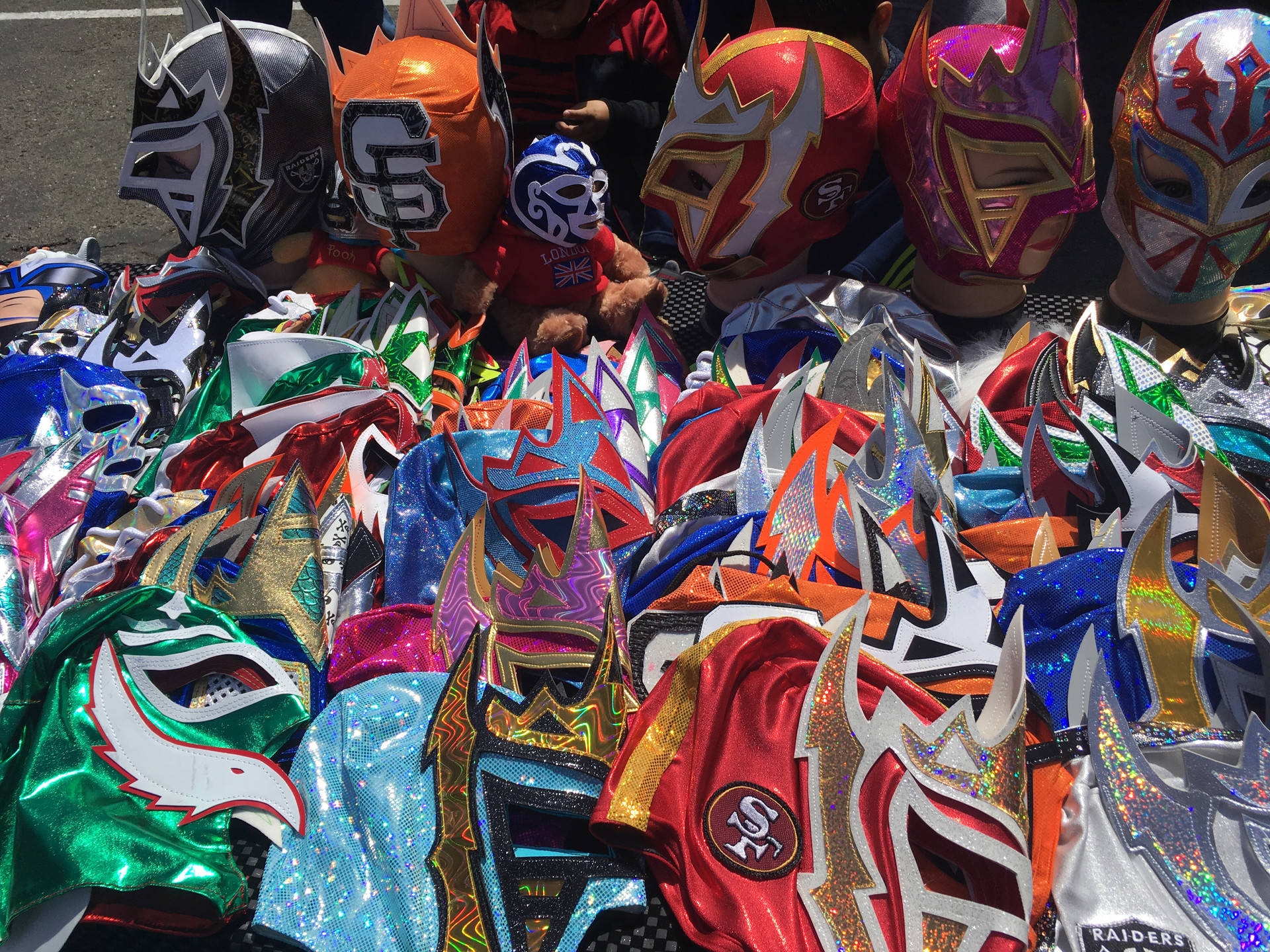 "A collection of luchador masks are put up for sale by Esmerelda Hernandez, the wife of ""Rockero del Diablo,"" one of the fighters at Lucha Libre Taco-con. Caroline Champlin/KQED"