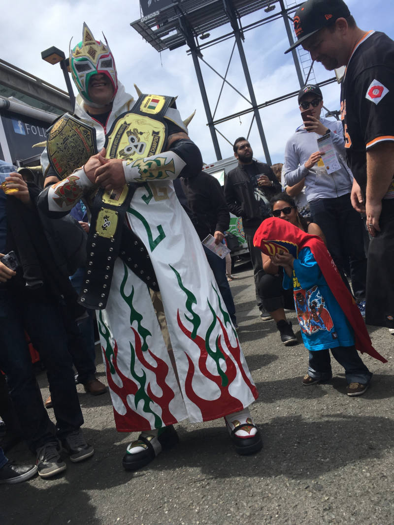 "Luchador ""Rockero Del Diablo"" carries his championship belts from previous fights. His wife says he's been fighting since he was 18."
