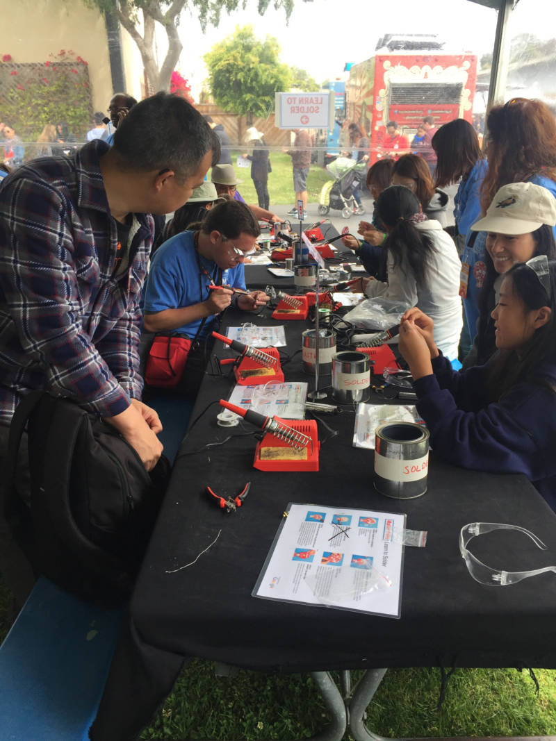 Makers of all ages work at the soldering table at the Maker Faire. The space allowed people of all ages to learn how to solder a battery and LED light to make a flashing button.