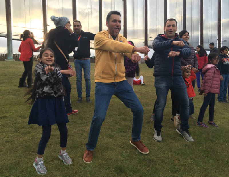 """Manu Singh (middle) of San José dances with his daughter, Sahana, to Benny Dayal's version of 'Gangnam Style. He says everybody can get into the """"peppy beats"""" of Indian music."""