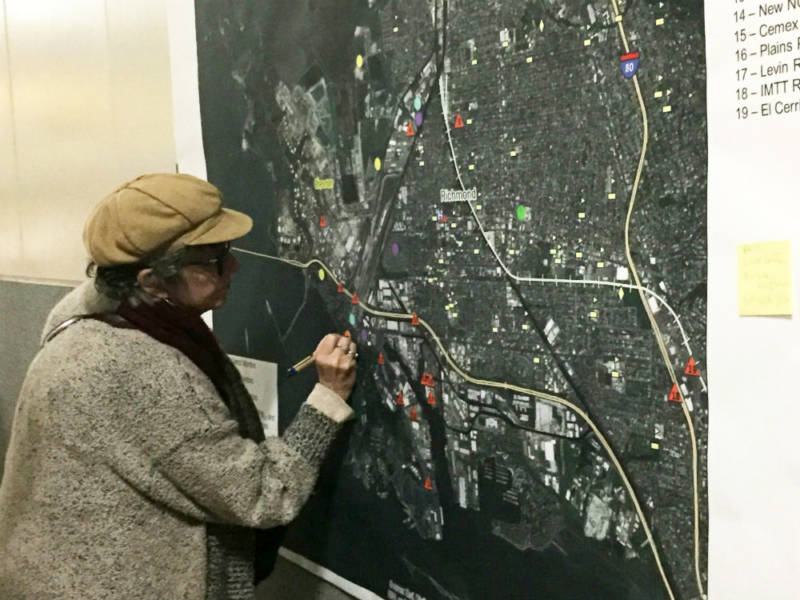 A woman marking up a map for air monitoring.