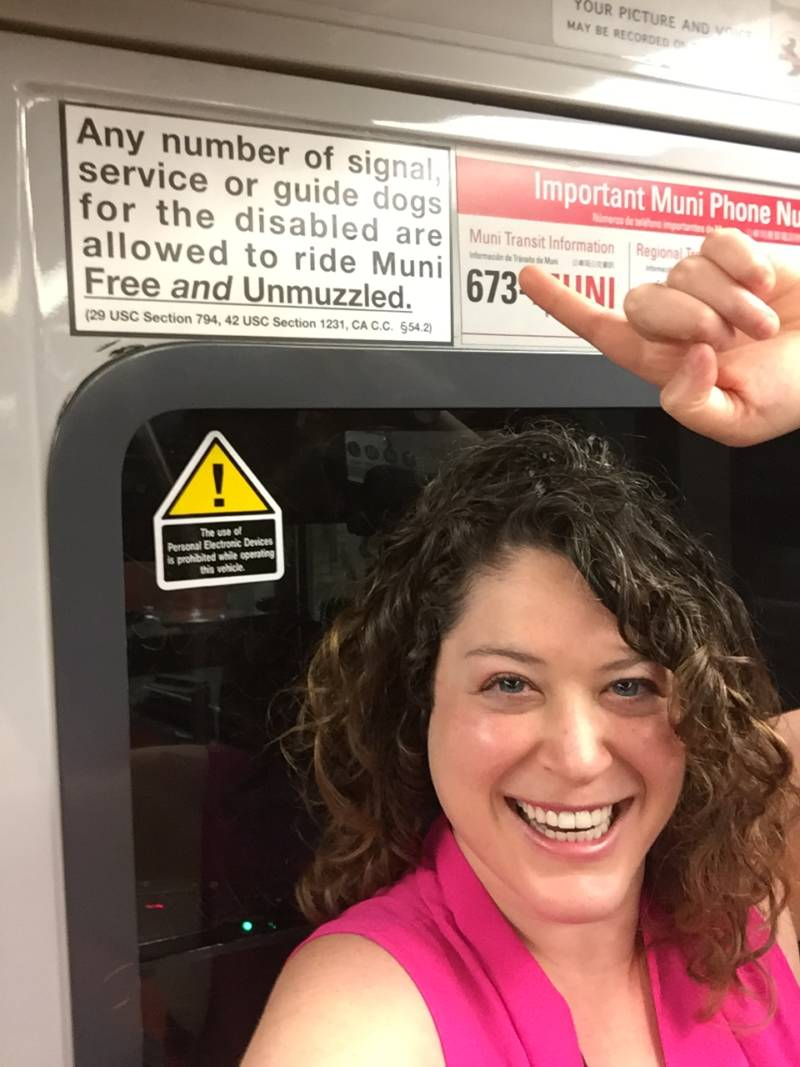 Bay Curious listener Rona Kramer stands next to a sign on the Muni Metro that says any number of service dogs can ride Muni.