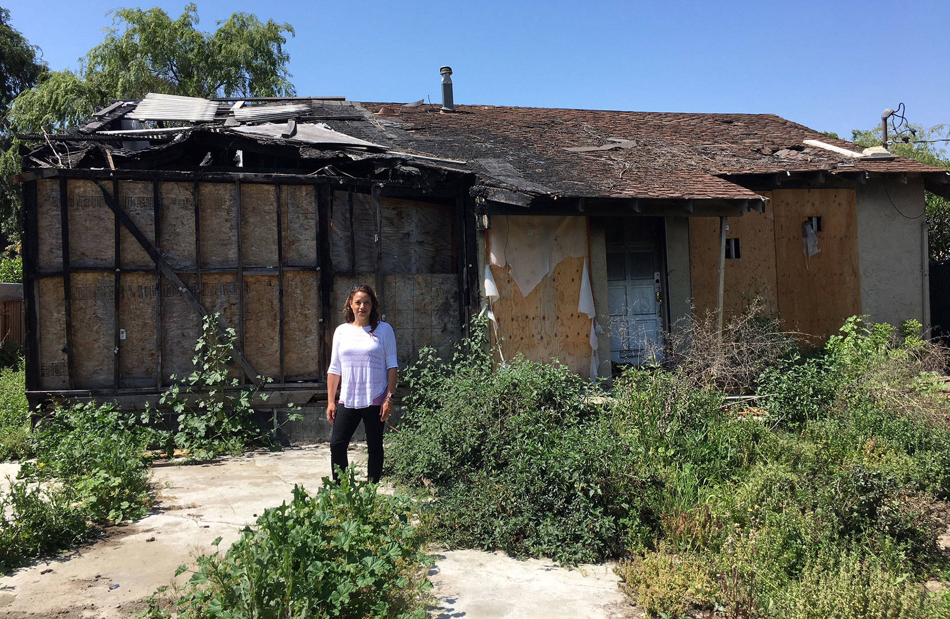 San Jose Realtor Holly Barr stands outside the burned-out house she sold for more than $900,000. Matt Levin/CALmatters
