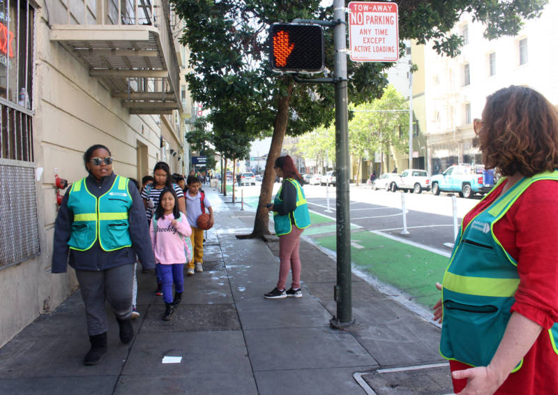 Kate Robinson (R) greets school children after Safe Passage volunteers cleared the Tenderloin sidewalk of people openly using drugs on April 24, 2018.