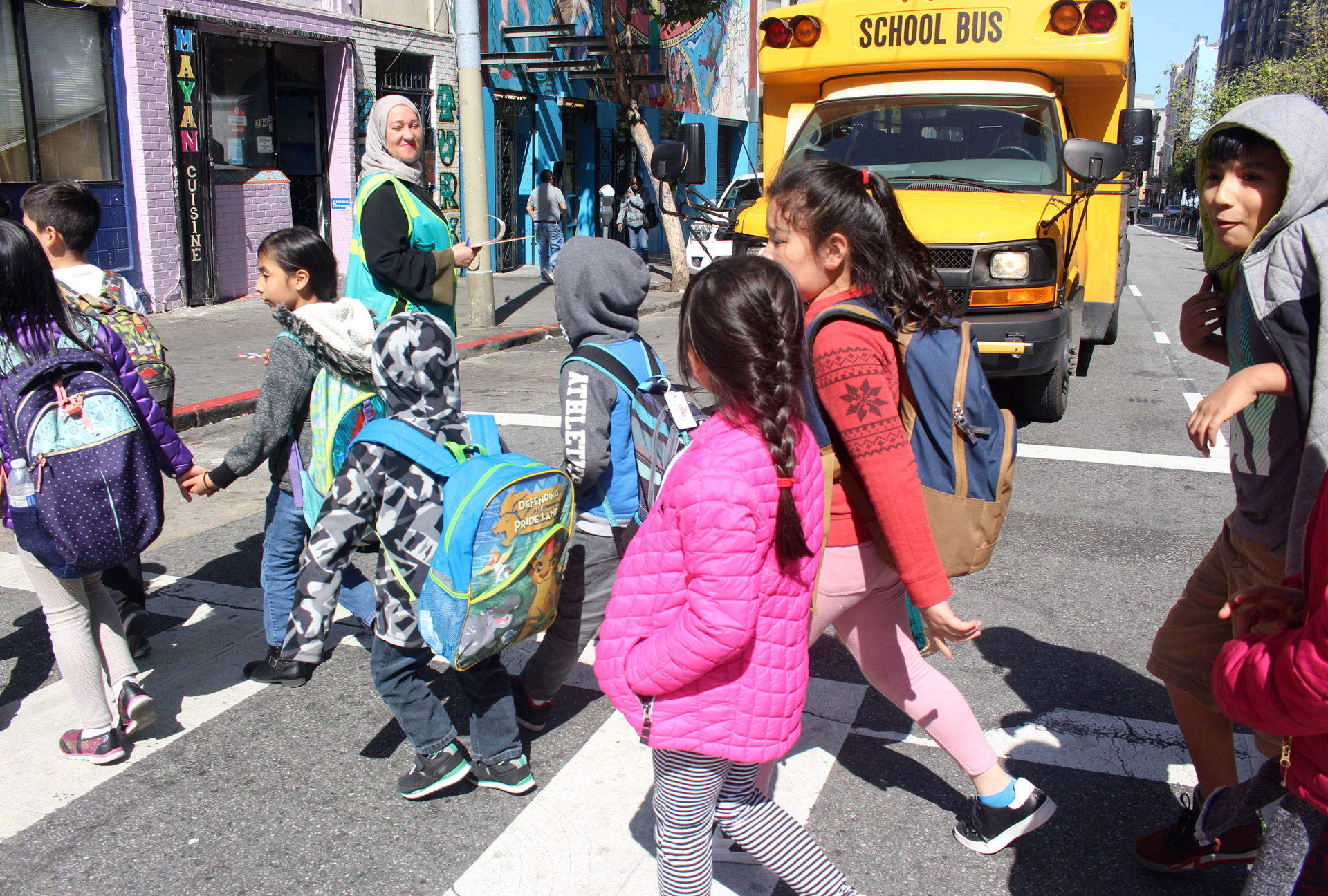 Elementary school students cross Turk Street in San Francisco as Safe Passage volunteer Tatiana Alabsi observes on April 24, 2018. Alabsi, a mom of two from Yemen, lives in affordable housing in the Tenderloin.