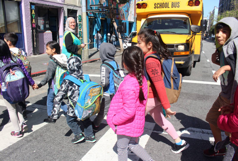 Elementary school students cross Turk Street in San Francisco as Safe Passage volunteer Tatiana Alabsi observes them on April 24, 2018.