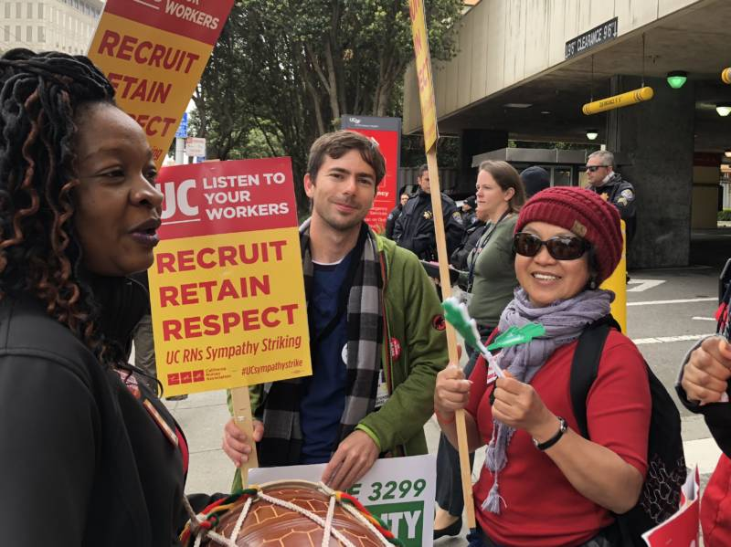 UCSF nurses Alicia Thomas, Al Davies, and Nalinee Tan carry signs and drum outside UCSF Parnassus Hospital on Tuesday, May 8, 2018.