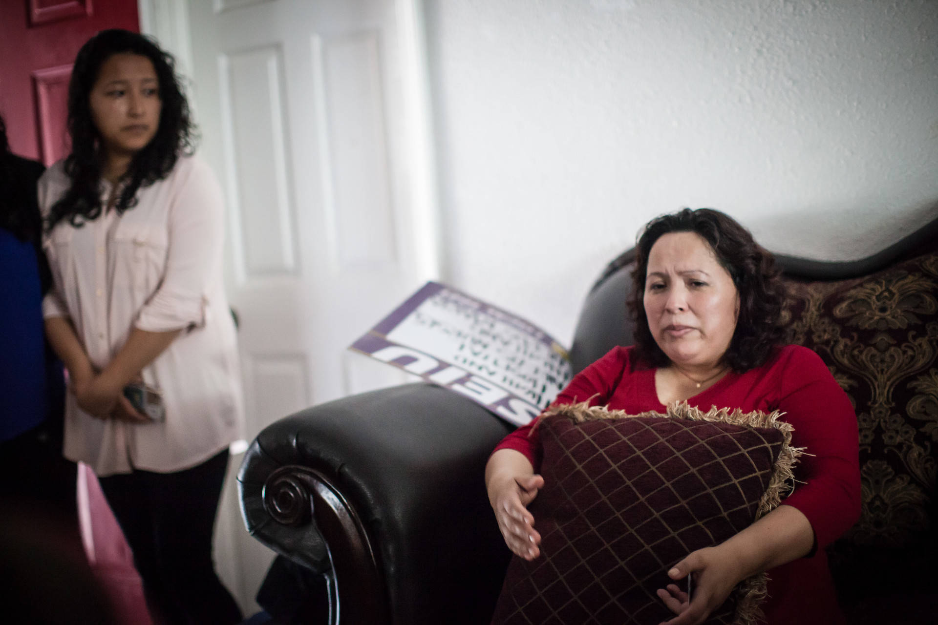 Maria Mendoza-Sanchez sits on a couch in her Oakland home on Aug. 16, 2017, hours before she, her husband and son leave Oakland for Mexico City. Her daughter, Melin Sanchez, 21, cries as she watches her mother with concern. Deborah Svoboda/KQED