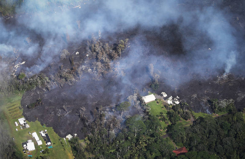 Lava from volcanic fissures slowly advances and overtakes structures and trees in the Leilani Estates neighborhood in Hawaii on Sunday. At least 26 homes have been destroyed by lava.