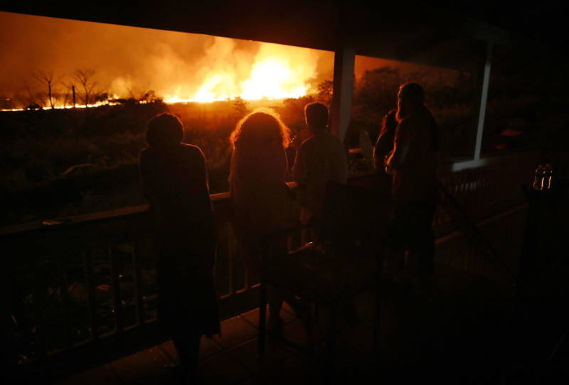 Residents view lava erupting from one of Kilauea's fissures, at a small viewing party on a neighbor's porch, on Hawaii's Big Island.