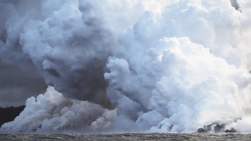 Steam plumes rise as lava from Kilauea enters the Pacific Ocean. Officials are warning residents to stay away from plumes of laze, which consists of hydrochloric acid and steam with fine glass particles.