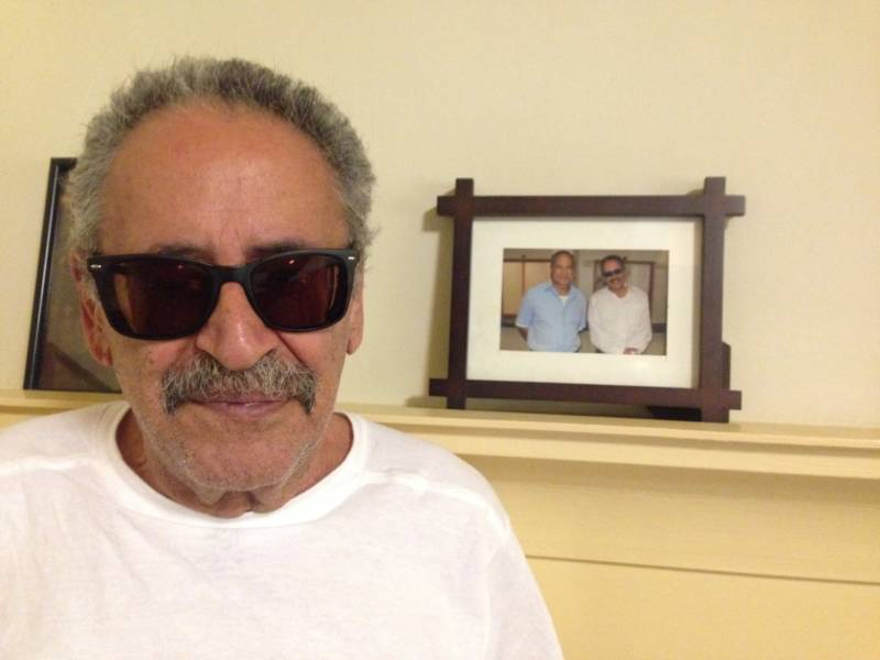 Munir Sirhan next to a photo taken during a prison visit with his brother Sirhan Sirhan.