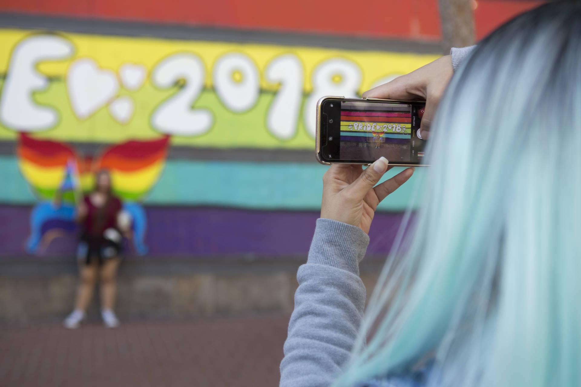 "Keila Cisneros takes a photo of her sister, Marina, in front of a mural on Market street that says ""Pride 2018."" ""I'm here to support my sister who just came out as bisexual and my best friend who is totally gay,"" said Cisneros with a giggle.  Anne Wernikoff/KQED"