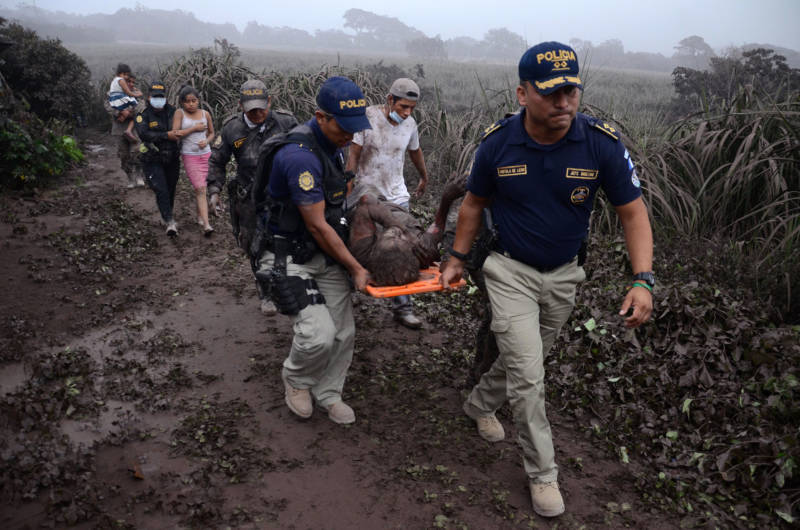 Police carry a wounded man after the eruption of the Fuego Volcano, in El Rodeo village, Escuintla department, on June 3, 2018.
