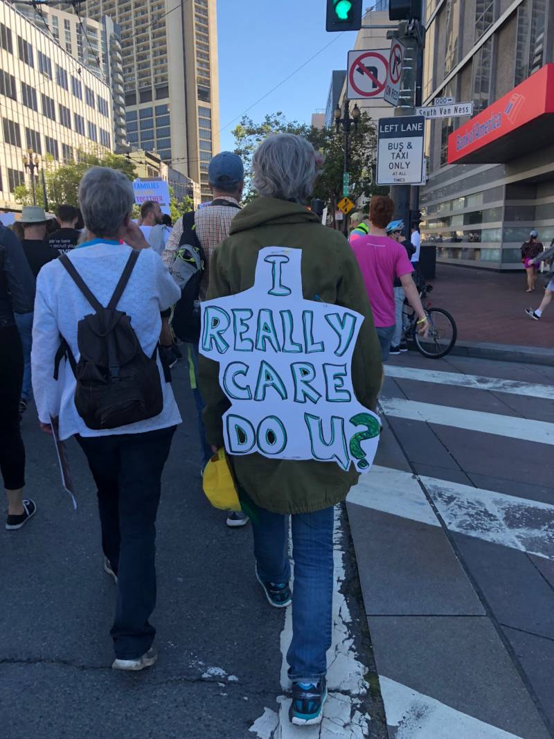 One marcher in San Francisco's 'Families Belong Together' march wears their sign.
