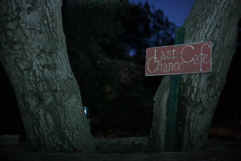 A sign hangs on a tree, marking a makeshift café.