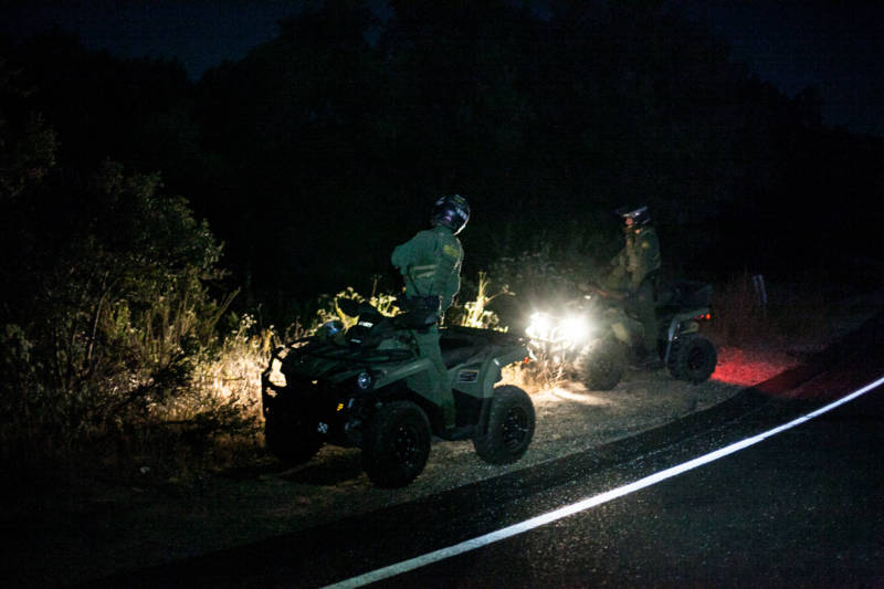 Early morning border patrol agents search for people near the Tecate - U.S. border. Someone left a marker for the people coming over to the U.S. side so they know where to go.