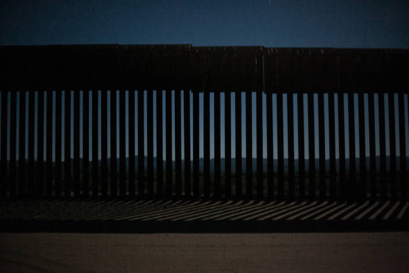 Looking through the metal fence from the U.S. side into Tecate, Mexico on June 28, 2018, before sunrise. The metal fence does not divide the U.S. and Mexico all the way, barbed wire is used as well.