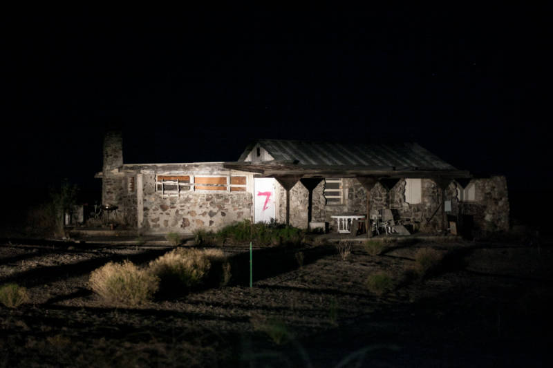 An abandoned home lit up with headlights located walking distance from the border fence that divides Tecate, Mexico and the U.S.