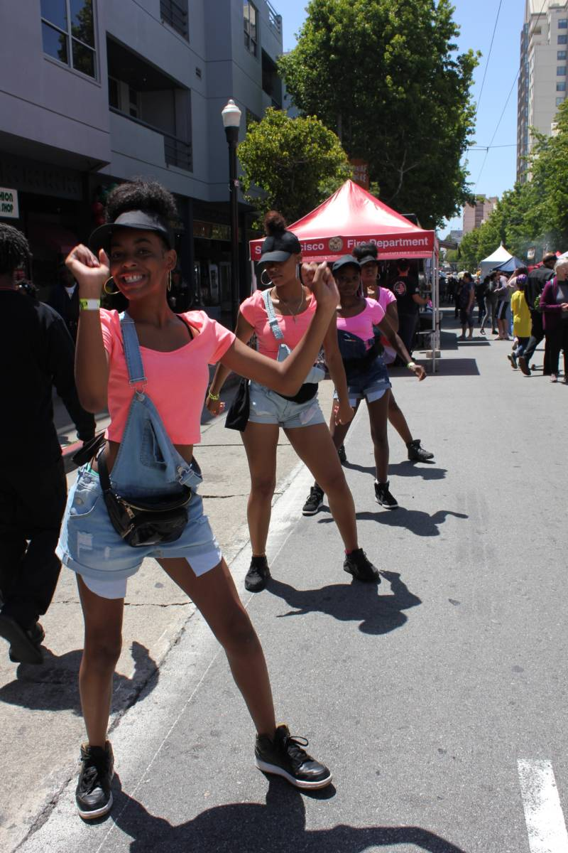 Members of the Lyric Performing Arts Academy dance down Fillmore Street as part of San Francisco's Juneteenth celebration.