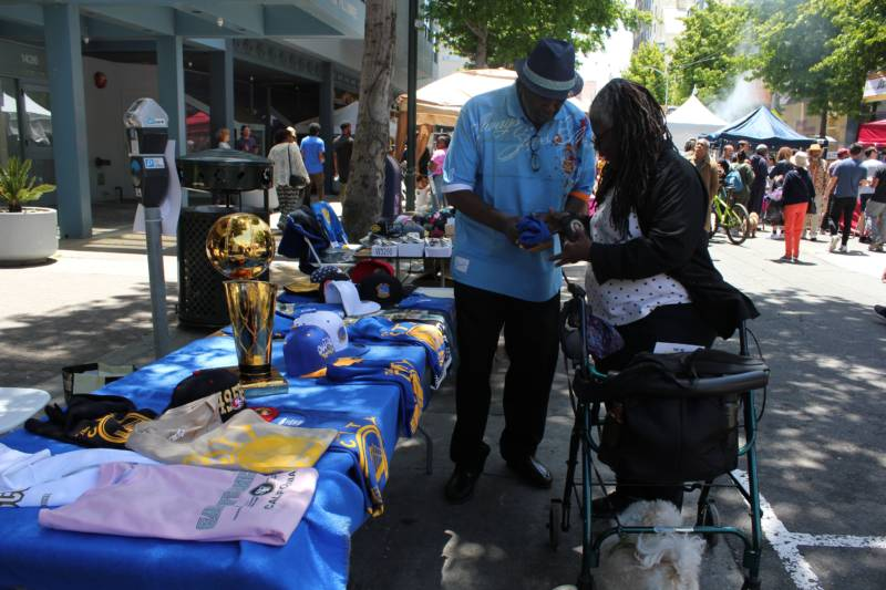 Rodrick Jones of San Francisco selling a Warriors t-shirt to neighbor Dianne Jordan. They both say they've been coming to the festival for years.