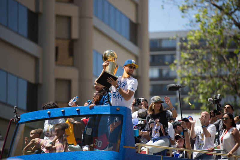 Stephen Curry carries the Larry O'Brien NBA Championship Trophy.