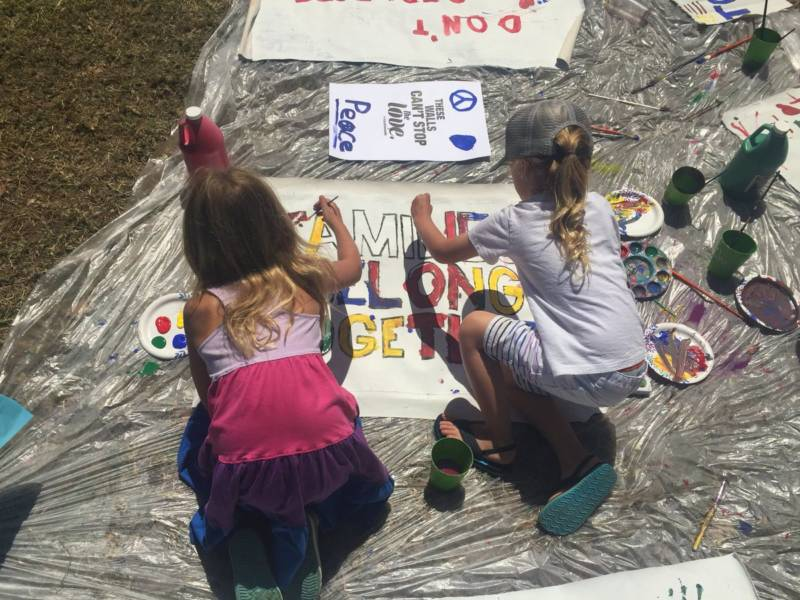 Elodie, age 7, and Jude, age 5, paint signs at the 'Families Belong Together' rally in Oakland.