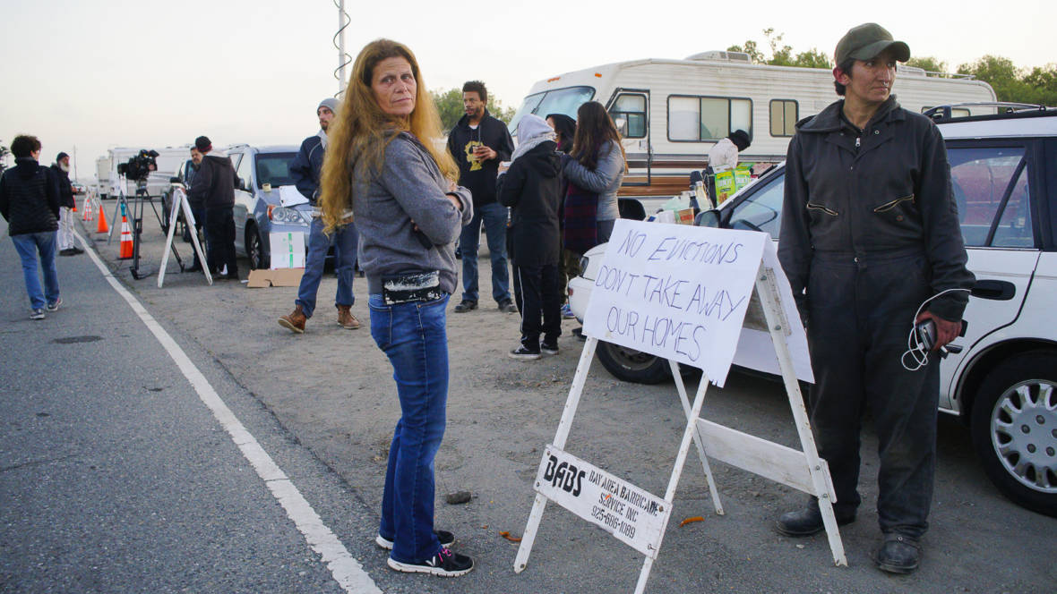 Amber Whitson and Pamela Benfante stand on the dirt lot next to Marina Boulevard on Memorial Day, waiting for Berkeley police to evict the vehicle community. Before 6 a.m. on that morning, a group of activists came to support the RV encampment and used their own vehicles to block the eight RVs still parked on the dirt lot.  Christian Torres/KQED