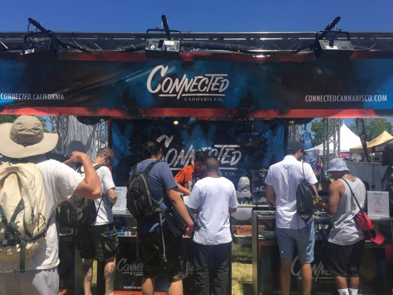 "Customers line up for some ""#designerweed"" from Connected Cannabis, one of the many corporate cannabis companies at the Cannabis Cup. Their booth had a DJ and a smoking lounge."